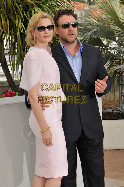 "CATE BLANCHETT & RUSSELL CROWE.""Robin Hood' photocall.63rd International Cannes Film Festival, France.12th May 2010.half 3/4 length pink skirt jacket sunglasses shades side blue black suit.CAP/PL.©Phil Loftus/Capital Pictures."