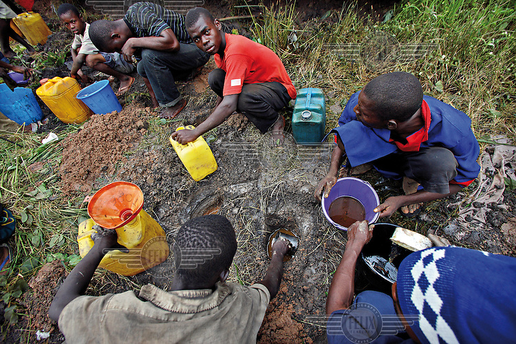 People collect oil rising up from beneath the surface of the ground..
