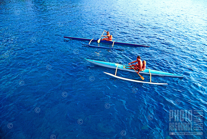 A family in two kayaks paddle in Kealakekua Bay on the Big Island of Hawaii. As of 2013 a moratorium halting all kaying in the bay has been issued by the Dept. of Land and Natural Resources. This could be revoked at anytime.
