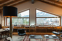 A pair of large windows afford the chalet's living room a spectacular view of the Alpine landscape