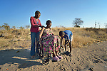 Delina Nleya rests after descending from a crowded kombi--a van used as public transportation--near her home in Bulawayo, Zimbabwe. With her is her daughter Nkazimulo, 16, and her son Davison, 14. People in wheelchairs in Zimbabwe are often ignored by kombi drivers, or they're charged double to bring their wheel chair along. Nleya suffered a spinal cord injury and uses a wheelchair provided by the Jairos Jiri Association with support from CBM-US.