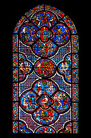 Medieval stained glass Window of the Gothic Cathedral of Chartres, France - dedicated to the Good Samaritan .  Bottom central panel shows Adam dwelling in Paradise, below - At the inn, the Samaritan nurses the injured man back to health, left - God breathing life into Adam, above - God warning Adam and Eve not to eat from the tree of knowledge, right - God creates Eve out of Adam's rib . Small central oval panel - Tempted by the serpent, Eve tastes the forbidden fruit , left side panel - Adam and Eve conversing beneath the tree of knowledge, right side panel -  God finds Adam and Eve hiding their nakedness. Top centre panel - God instructing Adam and Eve how to live in the wilderness, below - An angel casts Adam and Eve out of Paradise , left - Labouring in the wilderness; Adam digs and Eve spins, right -  Cain murdering his brother Abel with a sickle, above -  Christ in Majesty, seated on the rainbow. A UNESCO World Heritage Site.