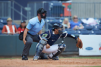 Gwinnett Stripers catcher John Ryan Murphy (12) sets a target as home plate umpire Chris Graham looks on during the game against the Scranton/Wilkes-Barre RailRiders at Coolray Field on August 18, 2019 in Lawrenceville, Georgia. The RailRiders defeated the Stripers 9-3. (Brian Westerholt/Four Seam Images)