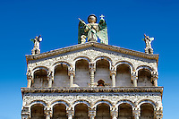 Upper arcades and statue of St Michele of the 13th century Romanesque facade of the San Michele in Foro,  a Roman Catholic basilica church in Lucca, Tunscany, Italy