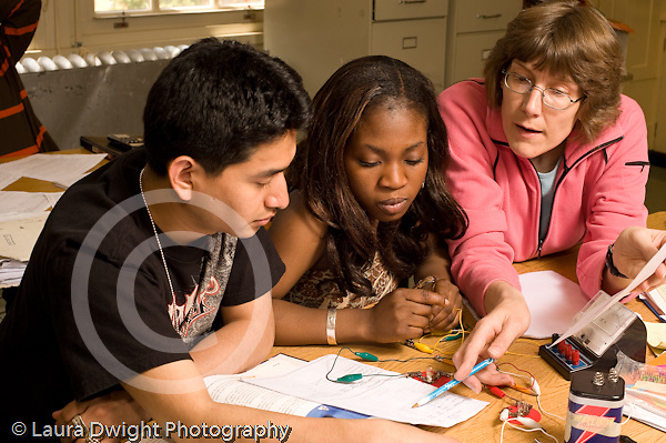 Education High School physics lab on electrical circuits female teacher working with male and female lab partners horizontal