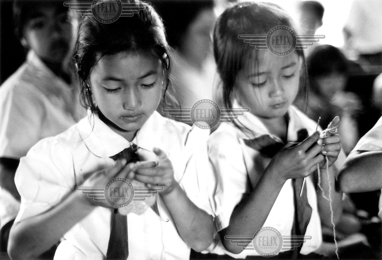 © Peter Barker / Panos Pictures..Laos...Girls crocheting in a state primary school.