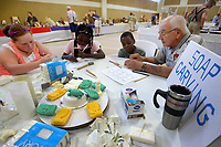 NWA Democrat-Gazette/BEN GOFF @NWABENGOFF<br /> Olivia Daepenbrock (from left), 12, of St. Louis, Mo., and twins Fernanda Frost and Renando Frost, 9, of Rockford, Ill. learn how to carve using butter knives and bars of soap with guidance from Larry Johnson of the Bella Vista Woodcarvers Club Saturday, July 15, 2017, during the Bella Vista Woodcarvers Club's Artistry in Wood Show at Bella Vista Assembly of God church. Members of the club exhibited and sold their woodwork at the show, which also included door prizes, demonstrations and a people's choice award.