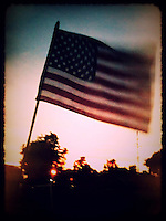 US Flag waves at sunset in an iPhone photo processed with a photo app