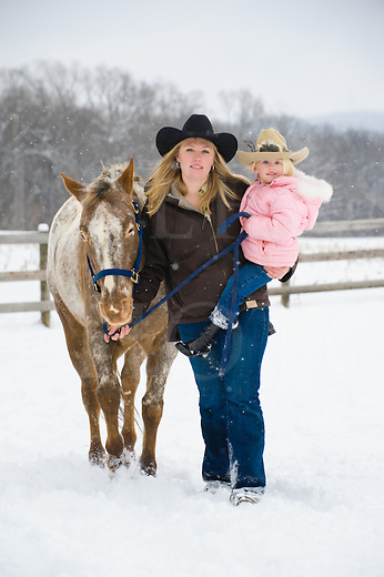Mother carrying small daughter and walking her Appaloosa horse through falling snow in a farm field, front view coming directly toward camera, Pennsylvania, PA, USA.