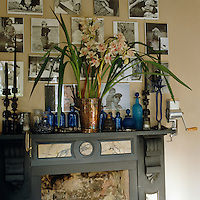 Black and white family photographs are pinned to the wall above a painted Victorian fireplace
