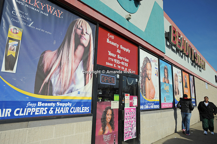 Women walk past a beauty supply store on 79th Street on the southern edge of the South Shore neighborhood of Chicago, Illinois on January 2, 2008.  Michelle Obama, wife of U.S. President Elect Barack Obama, was raised in a modest bungalow in the South Shore neighborhood on the South Side of Chicago.