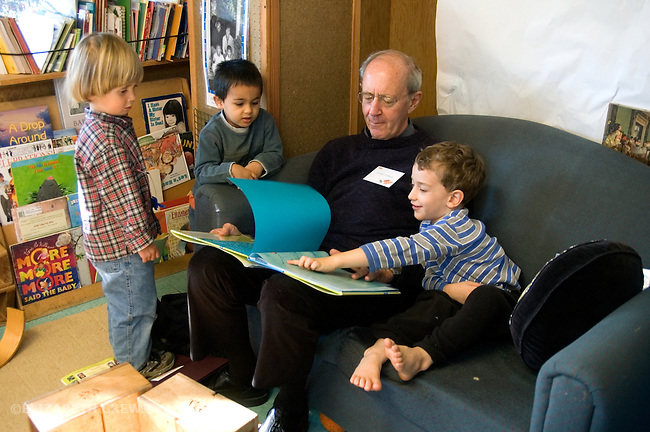 "Berkeley Ca Grandfather reading to four-year-old boys at preschool during visit on ""Grandparents' Day"""