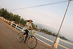 CAMBODIA  -  APRIL 3, 2005:  A woman riding a bicycle crosses the Kampot River on a bridge on April, 3, 2005 in Kampot, Cambodia. (PHOTOGRAPH BY MICHAEL NAGLE).