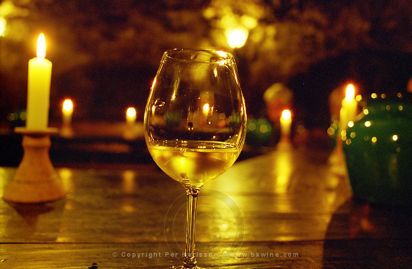 The Oremus winery in Tolcsva, Tokaj: In the underground tasting room, carved in the rock, a glass of Tokaj, lit by candles. People in the background tasting. Oremus is owned by the Alvarez family that also owns Vega Sicilia in Spain It is managed by Andras Bacso. Credit Per Karlsson BKWine.com
