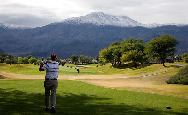GOLFER TEES OFF AT A PALM SPRINGS AREA GOLF COURSE AFTER A RECENT SNOWFALL IN THE NEARBY MOUNTAINS