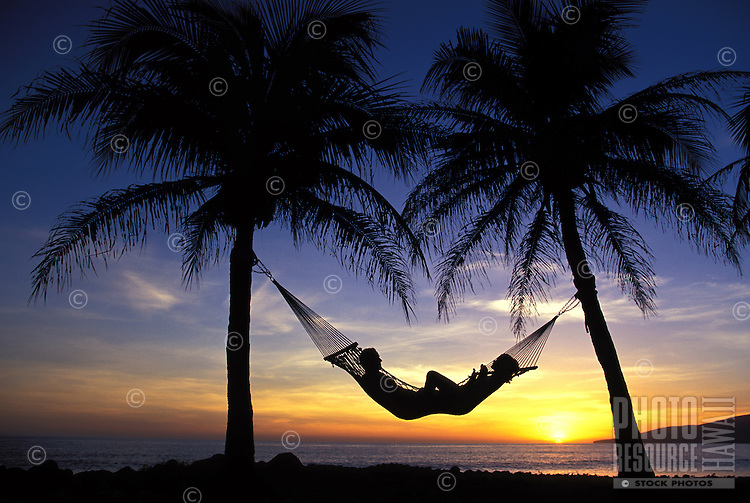 Couple enjoy a West Maui sunset in a hammock at Ka Puali, Maui.