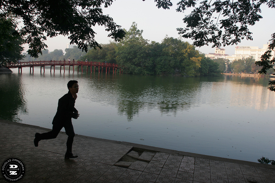 A man runs along Hoan Kiem Lake in Hanoi, Vietnam at sunrise.  In the background is Ngoc Son Temple on an island in the middle of the lake.  The lake is a popular place in the early morning for residents of the old quarter of Hanoi to jog, practice t'ai chi, or play badminton.  Photograph by Douglas ZImmerman