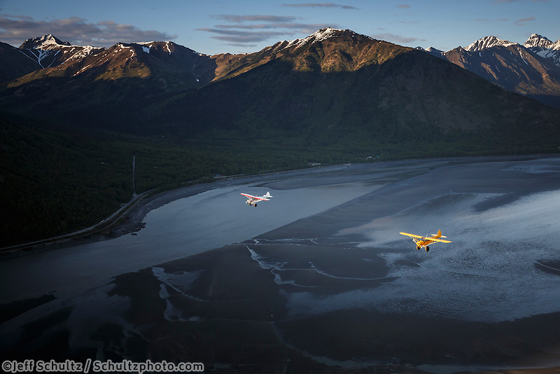 Super Cub airplanes fly over Turnagain Arm with Seward Highway and Chugach Mountains background<br />