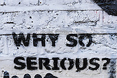 Spitalfields, London. Graffiti on a white painted brick wall: 'why so serious?'.