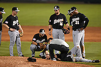 San Antonio Missions trainer Dan Turner checks pitcher Devin Jones (55) after being hit by a line drive as Brian Bixler (37), Jake Lemmerman (45), Jason Hagerty (16) and Francisco Morales (31) look on during a game against the Arkansas Travelers on May 24, 2014 at Dickey-Stephens Park in Little Rock, Arkansas.  Arkansas defeated San Antonio 4-2.  (Mike Janes/Four Seam Images)