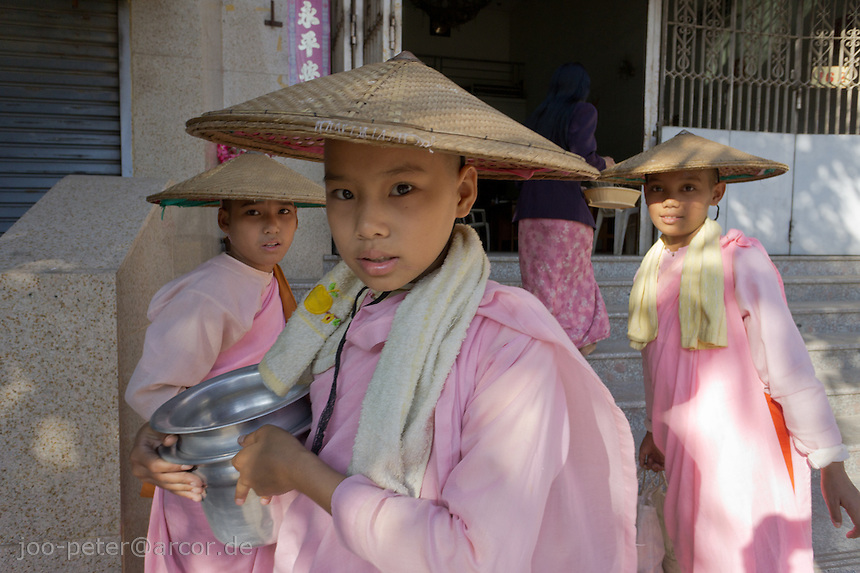 nuns in the streets of Mandalay, Myanmar, 2011.Nuns are called thilashin (posessor of morality). They shave their hair, wear pink robes and take a ordination similar as monks