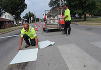 NWA Democrat-Gazette/FLIP PUTTHOFF<br /> Jim Northern (left) and Curtis Beasley with the Rogers Street Department place new crosswalk markers Tuesday Aug. 4 2015 at Sixth and Olive streets, near Northside Elementary school. Intersections near all Rogers schools are getting improvements, if needed, in anticipation of school starting Aug. 17, Beasley said. The tiles are similar to linoleum and last much longer than paint, he said.