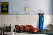19 year old Zamila Khatoon rests on the bed after giving birth to a premature baby in the delivery room of the Public Health Centre in Adapur village of Raxaul district of Bihar. Zamila's baby is 6 months old and weighs 800 gms.