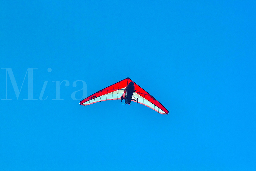 An ultralight airplane flys overhead.