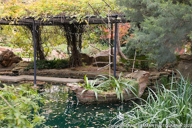 A boat shaped rock in a reflecting pool is festooned with bamboo sails in a fanciful construction at the Douglas Chandor Garden in Weatherford, Texas.