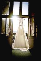 Sun shining through on to the beautiful Wedding Dress hanging up in the window at Eynsham Hall