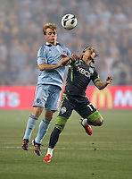 Seth Sinovic (16) of Sporting Kansas City fights for the ball with Fredy Montero (17) of the Seattle Sounders during the game at Livestrong Sporting Park in Kansas City, Kansas.   Sporting Kansas City won the Lamar Hunt U.S. Open Cup on penalty kicks after tying the Seattle Sounders in overtime.