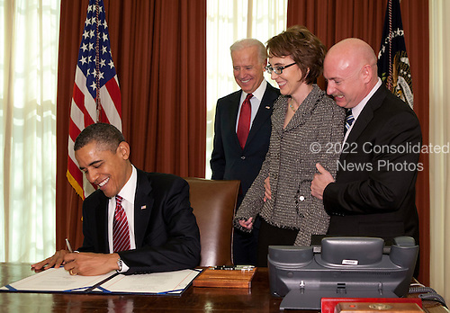United States President Barack Obama signs the Ultralight Aircraft Smuggling Prevention Act of 2012 as former U.S. Representative Gabrielle Giffords (Democrat of Arizona), her husband Mark Kelly, right, and Joseph Biden, second left, U.S. vice president, watch in the Oval office of the White House in Washington, DC, on February 10, 2012. The bill is the last piece of legislation that former Representative Gabrielle Giffords sponsored and voted on in the U.S. House of Representatives.   .Credit: Joshua Roberts / Pool via CNP