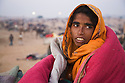 Woman huddled in blanket early morning at Pushkar camel fair; The annual Pushkar camel fair is one of the main tourist attractions in India, Pushkar, Rajasthan, India --- Model Released