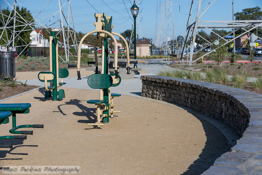 Greenfields outdoor bodyweight exercise equipment at State Street Park is surrounded by a bench/wall made out of broken up concrete.