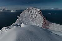 Fullmoon illuminates snow covered Veggen mountain peak, Vestvågøy, Lofoten Islands, Norway