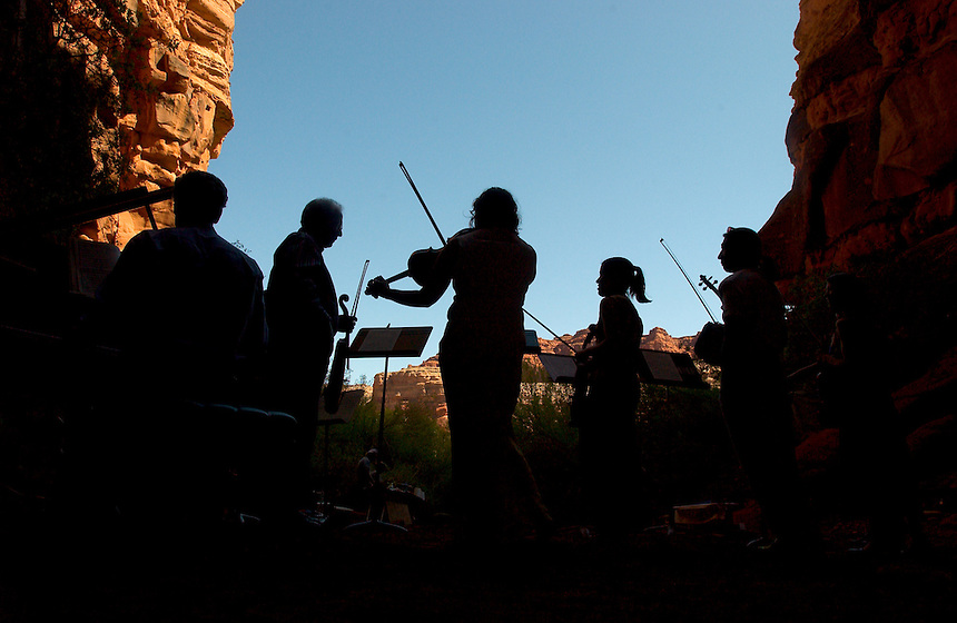 An orchestra launches into J.S. Bach's Brandenburg Concerto No. 3 in G Major on a wramup before a concert at a natural red rock grotto in a Colorado River canyon wall, for the Moab Music Festival in Moab, Utah, Thursday, Sept. 16, 2004. The group includes pianist Michael Barrett, left, violists Paul Hersh, Leslie Tomkins and Jennifer Frautschi, and violinist L.P. How. (Kevin Moloney for the New York Times)