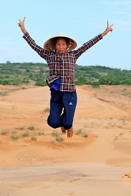 A woman hams it up for a snapshot at the red dunes near Mui Ne, Vietnam. Nov. 11, 2011.