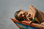 A girl smiles from a painted wooden boat on Phewa Lake near the Lakeside District in Pokhara, Nepal.