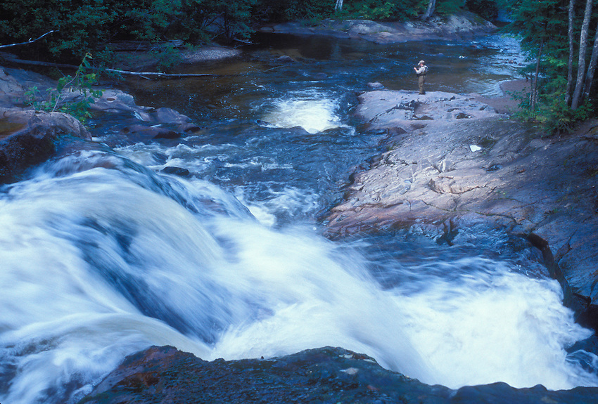 A woman fly fishes for trout below Yellow Dog Falls on the Yellow Dog River near Big Bay, Michigan.