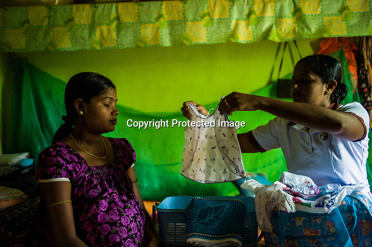 Mathumita (right) prepares the basket for Tuvarny, the 10 month pregnant expecting woman before she leaves for the hospital as part of the pre-natal programme during the field visits in Punaineeravi village in Kilinochchi in Northern Sri Lanka. Photo: Sanjit Das/Panos