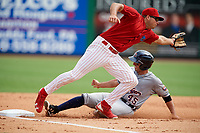Clearwater Threshers third baseman Damek Tomscha (21) stretches to try to receive an errant throw as Lakeland Flying Tigers catcher Arvicent Perez (45) slides into third base during the first game of a doubleheader against the Lakeland Flying Tigers on June 14, 2017 at Spectrum Field in Clearwater, Florida.  Lakeland defeated Clearwater 5-1.  (Mike Janes/Four Seam Images)