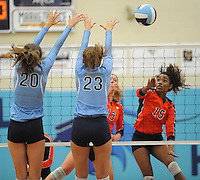 NWA Democrat-Gazette/ANDY SHUPE<br /> Shanice Erby (15) of Rogers Heritage sends the ball over the net as Emily Thompson (23) and Lauren Thompson (20) of Springdale Har-Ber defend Thursday, Sept. 17, 2015, at Wildcat Arena in Springdale. Visit nwadg.com/photos to see more photographs from the game.