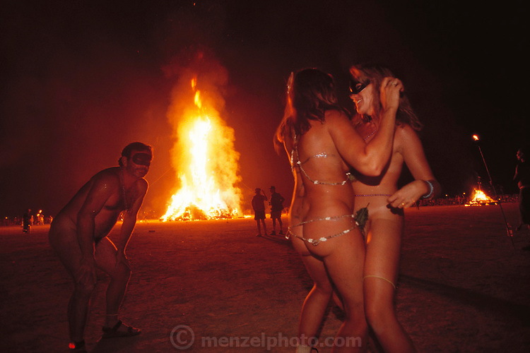 A man watches his girlfriend making it with another woman as the Burning Man burns. Burning Man is a performance art festival known for art, drugs and sex. It takes place annually in the Black Rock Desert near Gerlach, Nevada, USA.