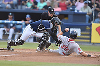 Asheville Tourists catcher Joel Diaz (5) puts the tag on a hard sliding Mitchell Gunsolus (22) as home plate umpire Sam Burch prepares to make the call during a game against the Greenville Drive at McCormick Field on April 14, 2017 in Asheville, North Carolina. The Drive defeated the Tourists 6-0. (Tony Farlow/Four Seam Images)