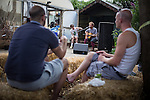 © Joel Goodman - 07973 332324 . 27 July 2013 . Hulme Community Garden Centre , Old Birley Street , Hulme , Manchester M15 , UK . Musicians play guitar and saw as visitors enjoy a Mojito in the sunshine . Hulme is Where the Art Is festival . Photo credit : Joel Goodman