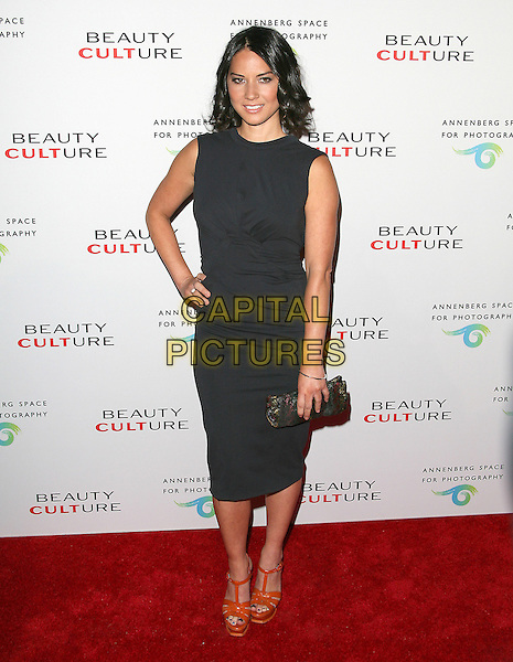 OLIVIA MUNN .at The opening of Beauty Culture - a photographic exploration of how feminine beauty is defined, challenged and revered in modern society held at Annenberg Space for Photography in Century City, California, USA,  .May 19th 11..full length dress hand on hip clutch bag sleeveless black orange platform ysl tribute shoes sandals                                     .CAP/RKE/DVS.©DVS/RockinExposures/Capital Pictures.