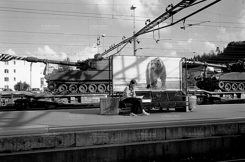Switzerland. Canton Zürich. View from the train between Zürich and Winterthur. A woman seats on a metal bench and reads a book. A poster of a brown bear. Two military tanks on a train's carriage. © 2005 Didier Ruef