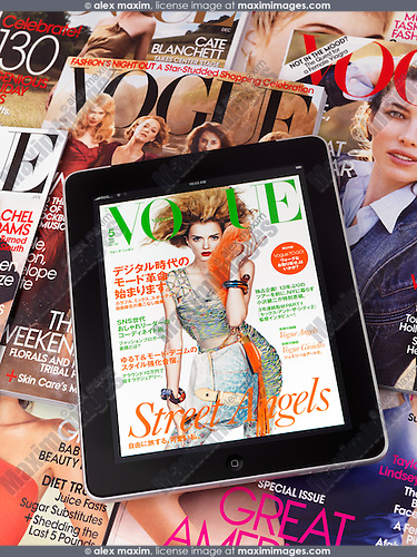 Apple iPad 3G tablet with an electronic issue of Vogue lying on top of printed Vogue fashion magazines