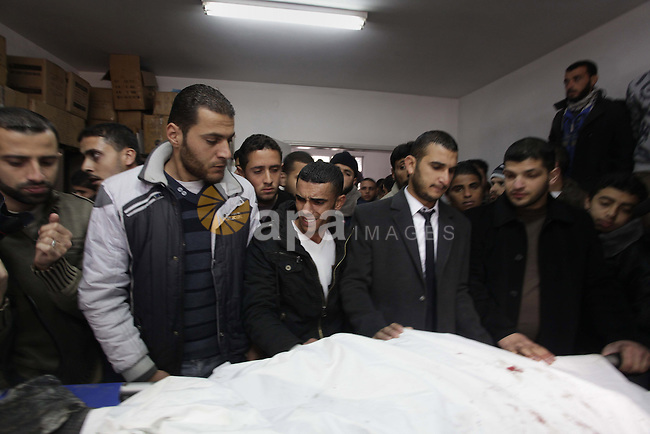 Palestinians gather around the body of Mohammed Al-Ejla ,32, at Al-shifa hospital Gaza city on Jan. 08, 2014.  A man was killed on Wednesday in the Gaza Strip after Israeli tanks fired at an area east of Gaza City, medical sources said. Photo by Ashraf Amra