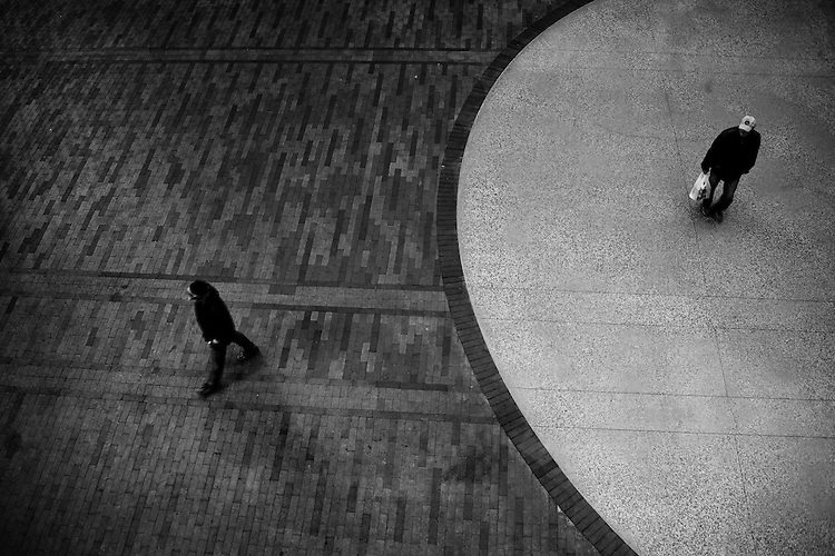 Two people  in urban environment  walking seen from above along a patterned floor with a circle.